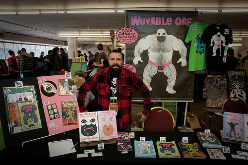 Wuvable Oaf creator Ed Luce in front of his oafy posters and products